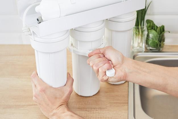 Encanador ou mão de homem substituir os cartuchos de filtro de água. corrija o sistema de osmose de purificação.