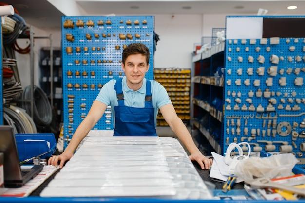 Encanador posa no balcão, escolhendo a loja de encanamento. homem comprando ferramentas e equipamentos de engenharia sanitária na loja