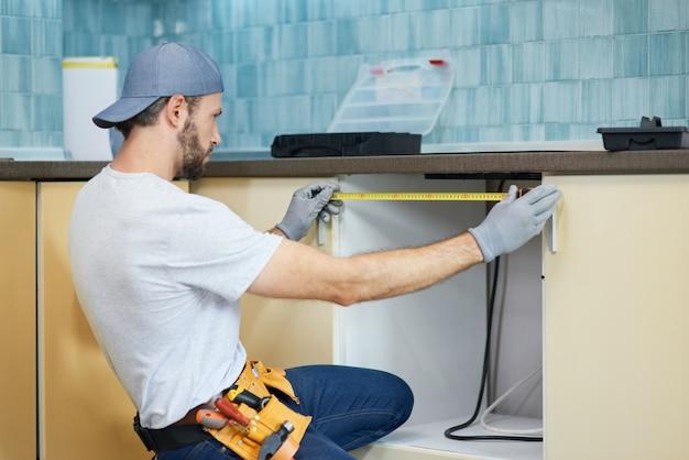 Encanador profissional jovem reparador usando fita métrica enquanto trabalhava no encanamento em um apartamento novo