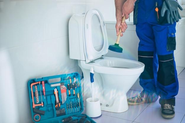 Encanador profissional uniformizado conserta o vaso sanitário do banheiro doméstico com a ajuda de ferramentas