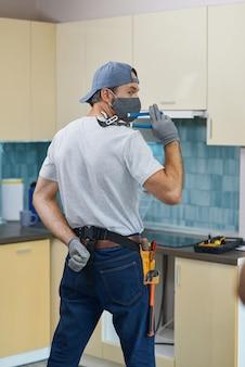 Encanador reparador profissional usando uma máscara posando com uma chave inglesa enquanto se prepara para