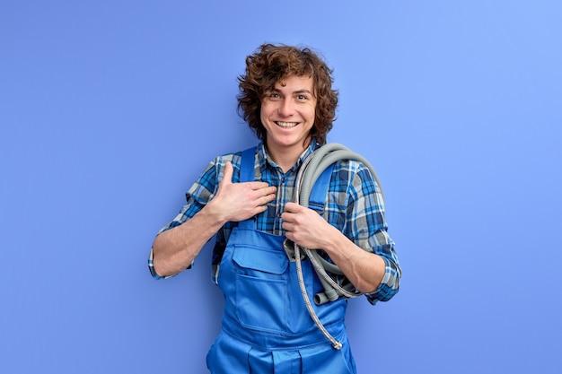 Encanador se surpreende com agradecimentos de clientes, olhando para a câmera com felicidade, vestindo avental azul