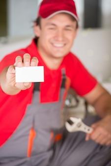 Encanador segurando uma chave inglesa na mão e mostrando o cartão de visita.