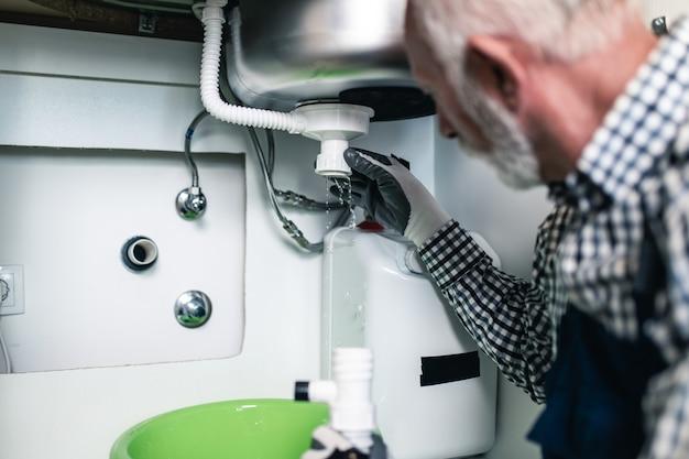Encanador sênior trabalhando com ferramentas de encanamento na cozinha. renovação.