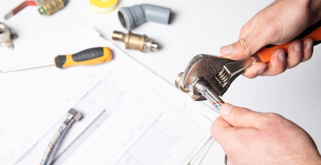 Encanador trabalhador mãos aparafusando a porca do tubo