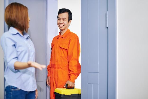 Encanador vietnamita sorridente com caixa de ferramentas entrando no apartamento de uma jovem