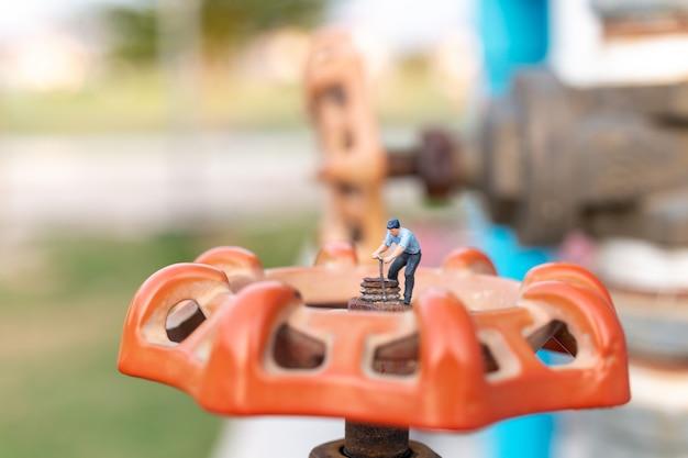 Encanadores de trabalho instalam tubulações de água e verificam danos a máquinas de bombas de água