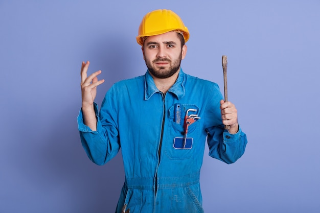 Encanadores masculinos intrigados ou mecânico de automóveis não conseguem entender onde está a quebra, encolher os ombros e levantar as mãos em perplexidade