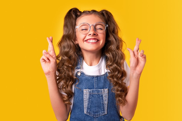 Encantada e esperançosa estudante adolescente de macacão jeans e óculos, mantendo os olhos fechados e cruzando os dedos enquanto deseja boa sorte