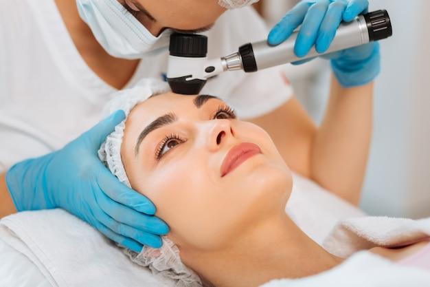 Encantada mulher simpática tendo sua pele examinada durante uma visita a um dermatologista