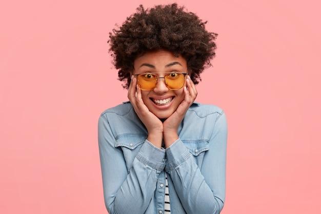 Encantada, positiva, linda mulher de pele escura toca as bochechas, sorri feliz ao ouvir a piada de um amigo, expressa positividade, tem penteado afro, vestida com jaqueta jeans, isolada na parede rosa
