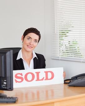 Encantador agente imobiliário com um painel vendido