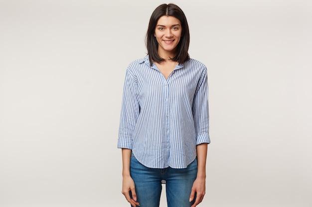 Encantador atraente sorridente jovem morena agradável em pé isolado, vestido com jeans e camisa listrada.