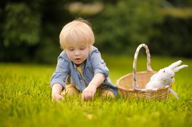 Encantador garotinho caça ovo de páscoa no parque primavera no dia de páscoa.