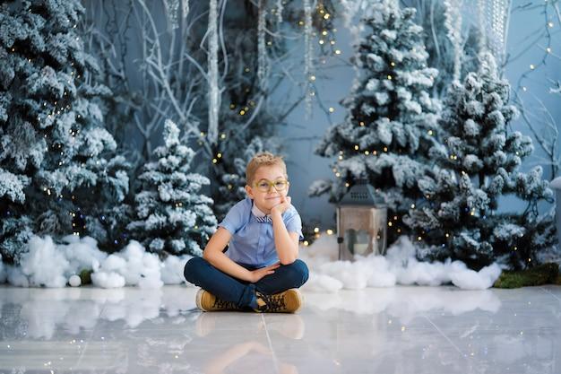 Encantador garotinho está sentado em casa, inverno nevado decorada árvore no fundo