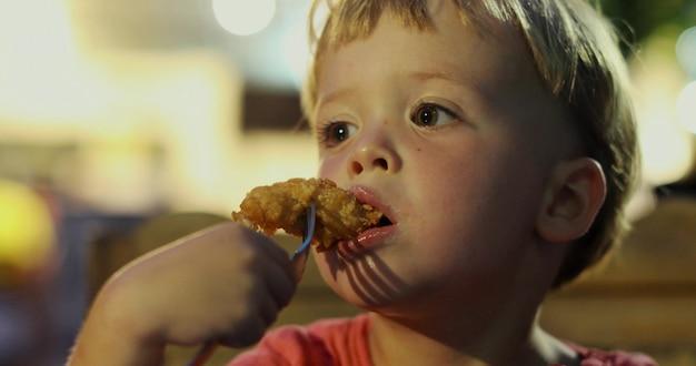 Encantador menino sonhador olhando para longe e mordendo nuggets de frango saboroso enquanto está sentado no fundo desfocado do café