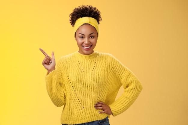 Encantadora atrevida elegante garota afro-americana em suéter apontando o canto superior esquerdo em pé confiante atrevido sorriso energizado fundo amarelo promovendo mercadoria mostrando a melhor escolha de câmera de olhar divertido.