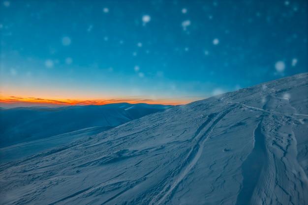 Encantadora bela vista das montanhas e colinas no vale nevado no final da noite. conceito de beleza da paisagem de inverno e relaxamento de fim de semana de inverno. copyspace
