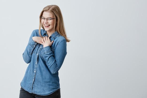 Encantadora brincalhão coquete europeu feminino jovem com cabelos lisos loiros sorrindo como se estivesse flertando. menina bonita vestindo óculos e camisa jeans com expressão alegre no rosto