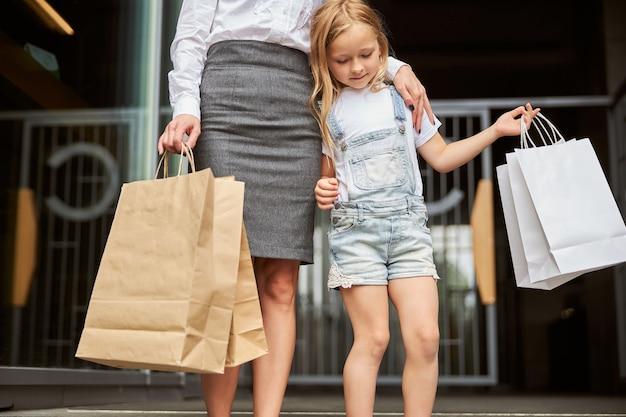 Encantadora criança do sexo feminino com sacolas de papel passando um tempo no centro da cidade