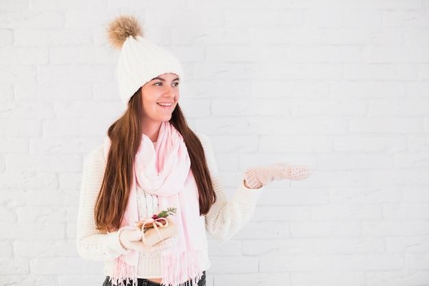 Encantadora dama em luvas, bobble chapéu e cachecol com caixa de presente e mão aberta