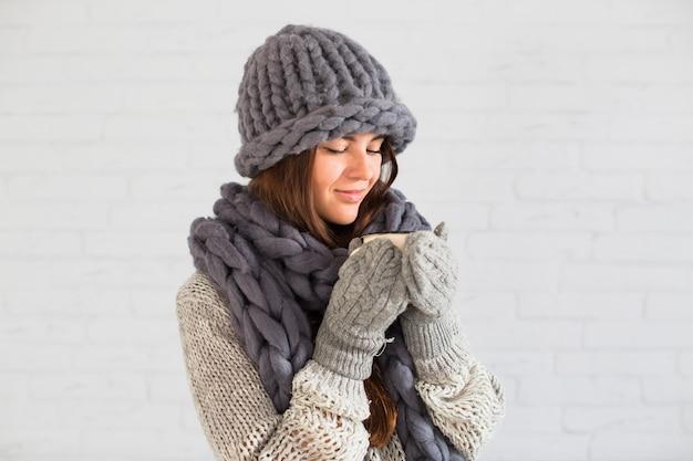 Encantadora dama em luvas, chapéu e cachecol com copo nas mãos