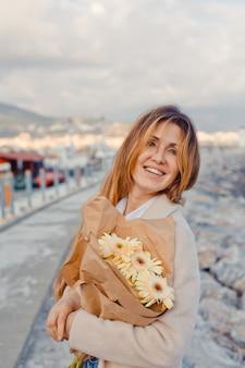 Encantadora dama em pé sorrindo com flores na beira-mar durante a tarde ee olhando alegre.