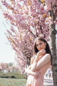 Encantadora dama posando na câmera perto de árvore de sakura