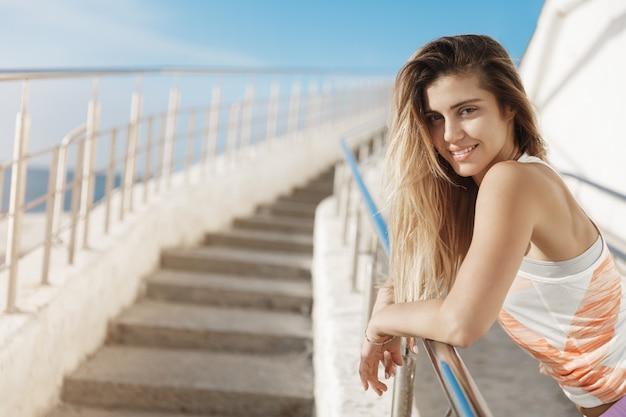 Encantadora e alegre corredora encostada na barra de metal sorrindo, descansando após um treino produtivo