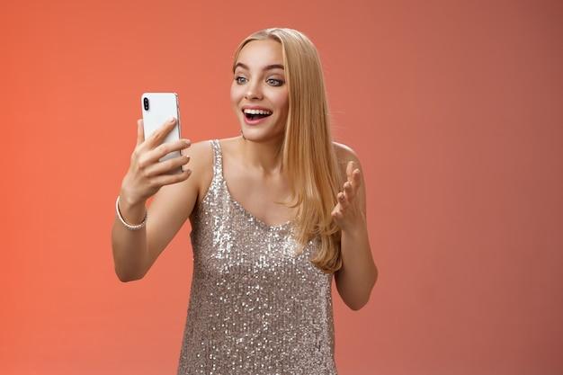Encantadora elegante garota loira legal em um vestido prateado falando de videochamada falando procurando tela de smartphone divertida, surpresa, sorrindo alegremente conversando com irmão mostrando roupa de baile.