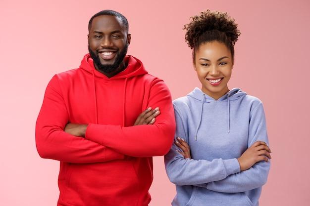 Encantadora equipe profissional feliz, dois afro-americanos, uma garota sorridente, amplamente autoconfiante, habilidades próprias, braços cruzados, peito, sorrindo, amigável, imbatível, trabalhando juntos, em pé, fundo rosa