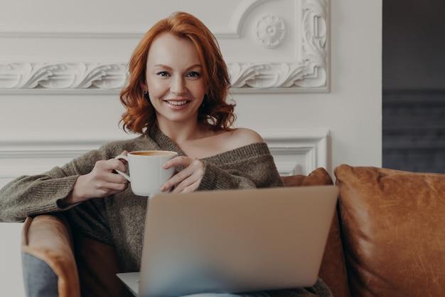 Encantadora fêmea de gengibre senta-se em um sofá confortável com uma xícara de café procura nova vaga de emprego