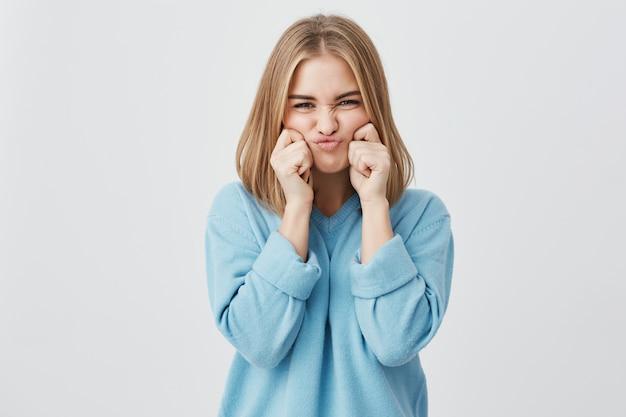 Encantadora, franzindo a testa, jovem mulher européia com cabelo loiro, suéter azul, beliscando as bochechas, zombando, tendo bom humor e diversão.