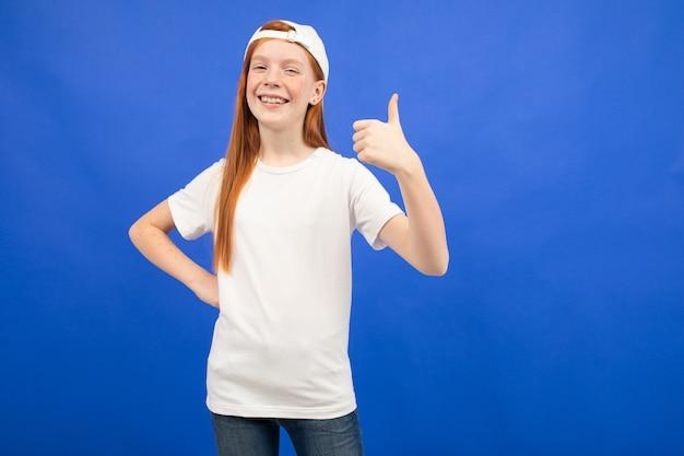Encantadora garota adolescente ruiva em uma camiseta branca com um layout mostra uma super classe polegares para cima azul