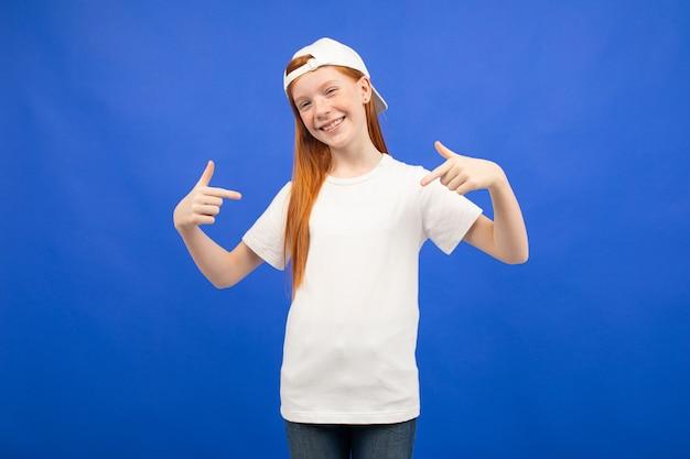 Encantadora garota adolescente ruiva em uma camiseta branca com uma maquete de impressão azul