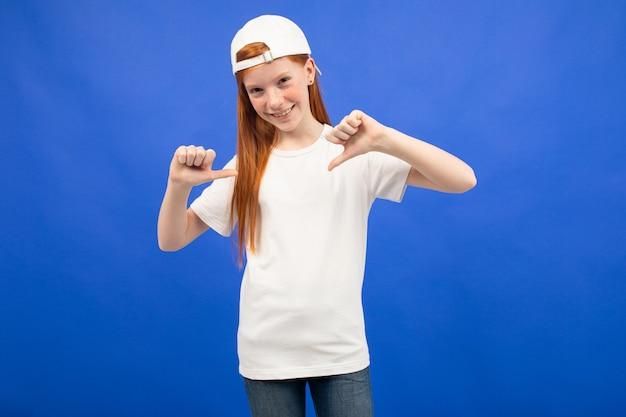 Encantadora garota adolescente ruiva em uma camiseta branca com uma maquete sobre um fundo azul do estúdio