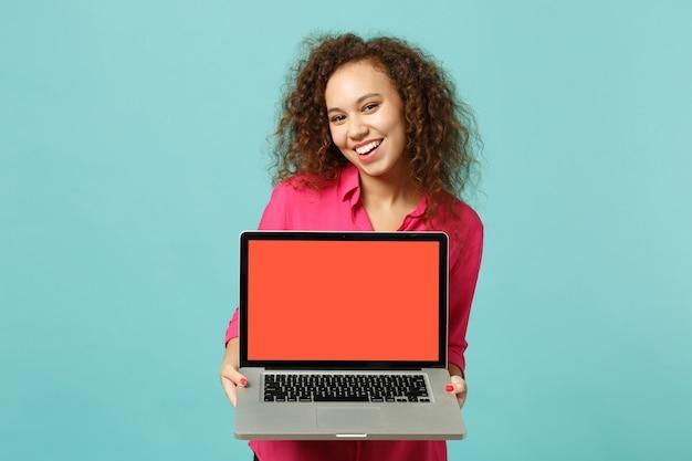Encantadora garota africana com roupas casuais segurar o computador laptop pc com a tela em branco vazia isolada no fundo azul turquesa no estúdio. emoções sinceras de pessoas, conceito de estilo de vida. simule o espaço da cópia.