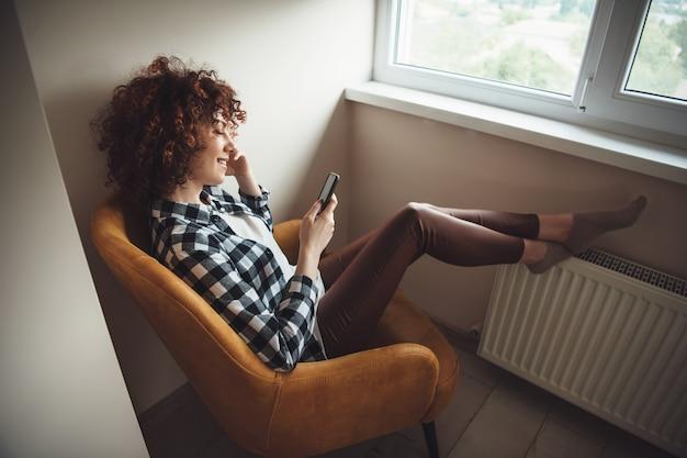 Encantadora garota caucasiana com cabelo encaracolado sentada na poltrona e sorrindo enquanto conversa no celular