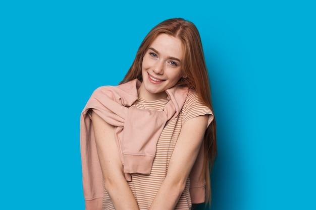 Encantadora garota caucasiana com cabelo vermelho e um lindo sorriso posando inocentemente em um fundo azul