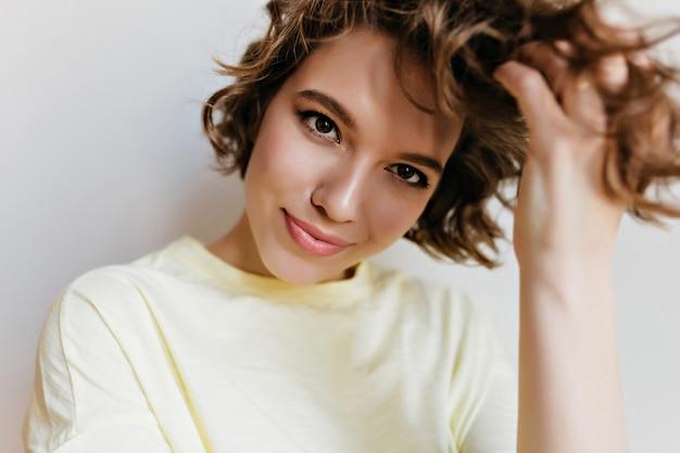 Encantadora garota caucasiana isolada na parede branca. retrato interno da moça bonita brincando com cabelo escuro curto, com um sorriso gentil.