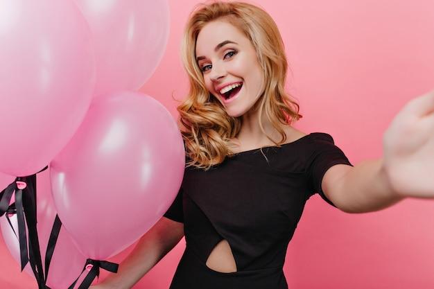 Encantadora garota de cabelos louros com maquiagem elegante, fazendo selfie na festa. mulher jovem rindo com balões, apreciando o evento.