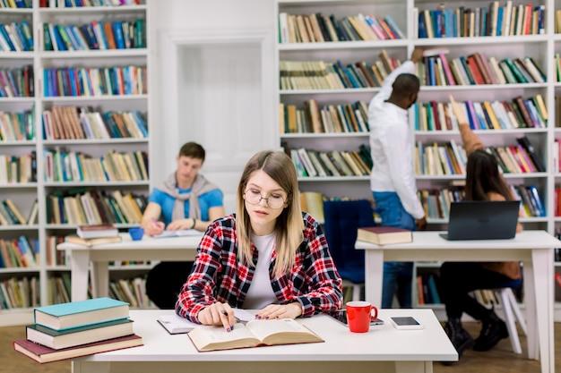 Encantadora garota moderna inteligente de óculos e camisa quadriculada, escrevendo notas do livro, enquanto se prepara para os exames na sala de leitura da biblioteca da faculdade. pessoas multiétnicas no espaço