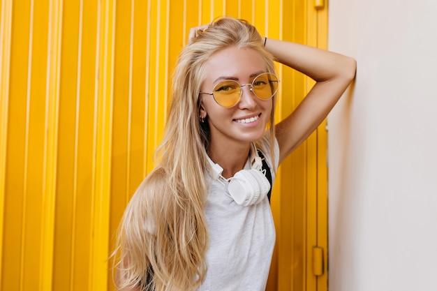 Encantadora garota sorridente de cabelos compridos em óculos de sol amarelos.