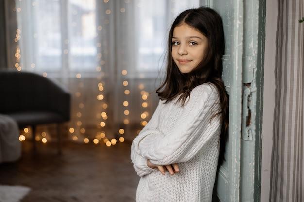 Encantadora jovem adolescente na camisola branca e calça jeans coloca na sala com decoração de natal