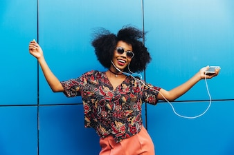 Encantadora jovem americana afro incrível em óculos de sol, dançando