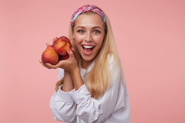 Encantadora jovem animada com longos cabelos loiros, olhando e segurando pêssegos nas mãos, isolado