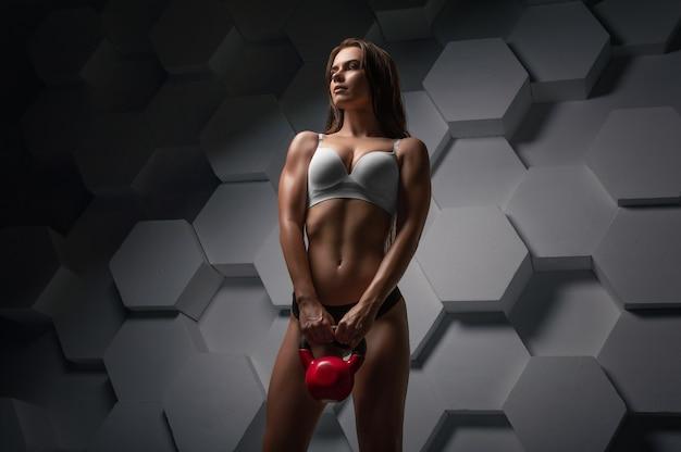 Encantadora jovem atleta posando com um kettlebell. conceito de aptidão. mídia mista