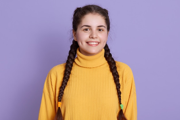 Encantadora jovem covinha com duas tranças posando contra parede lilás, vestindo blusa amarela