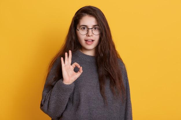 Encantadora jovem de cabelos escuros veste camisola preta mostrando sinal de ok com os dedos