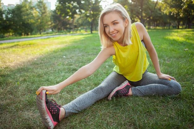 Encantadora jovem desportista exercitando no parque de manhã